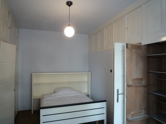 Des rangements séparent la chambre de la salle de séjour.
