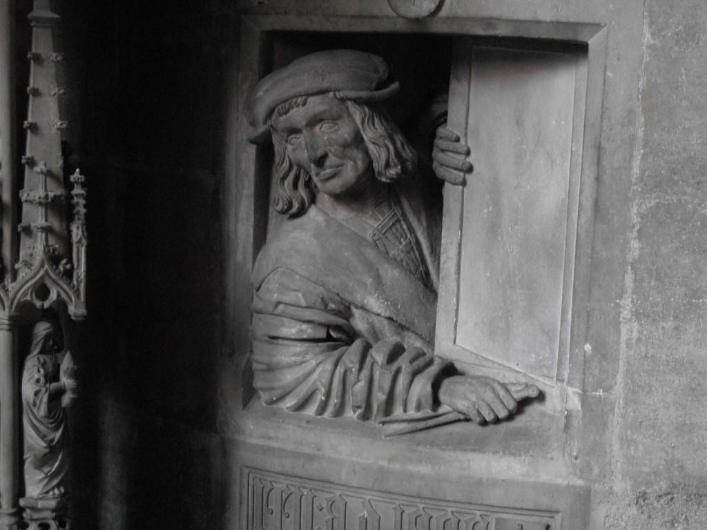 L'architecte s'est représenté regardant par la fenêtre avec ses attributs (compas et son équerre)