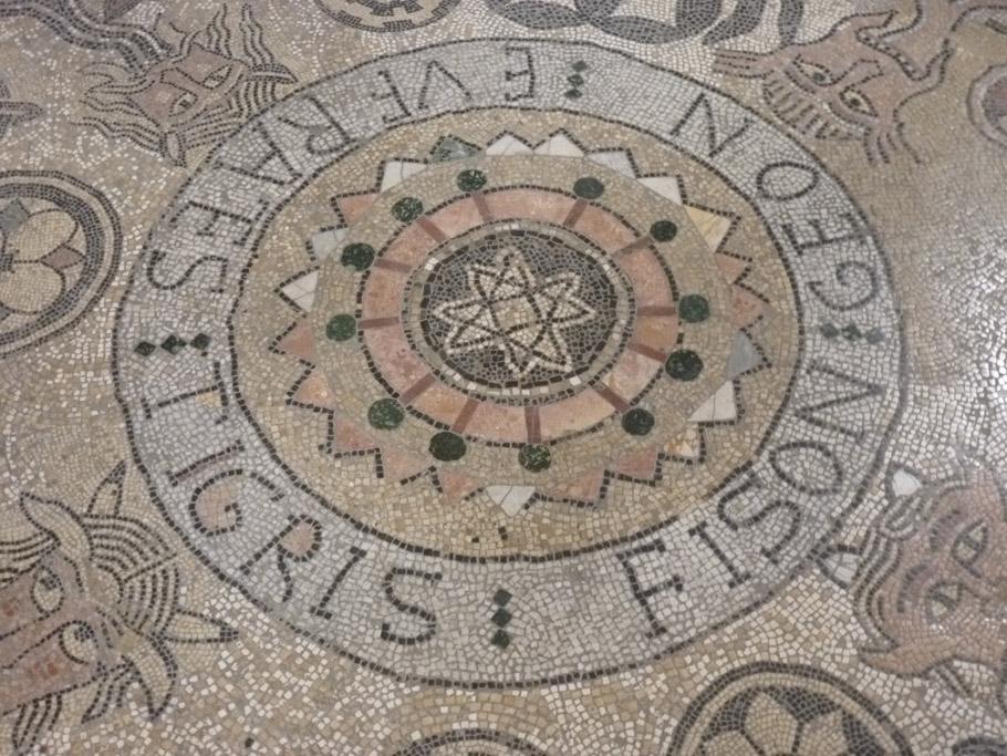 Au centre du médaillon, une étoile à huit branches (étoile polaire?), à son extrémité le nom des quatre fleuves du paradis