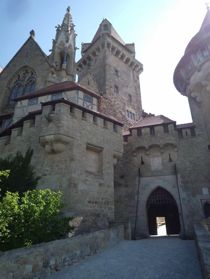 L'entrée principale est accessible par un pont en pierre (en arrière plan: la chapelle et le donjon)
