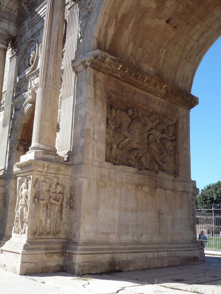 """Le côté Ouest de l'intérieur de l'arcade centrale avec l'inscription """"LIBERATORI · VRBIS"""" (libérateur de la cité) au dessus d'un fragment de frise représentant la conquête d'un village dace par la cavalerie et l'infanterie romaine qui poussent les prisonniers."""