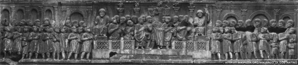 """Le relief à gauche de la façade Nord représentant le discours de Constantin depuis les Rostres. On y voit distinctement plusieurs constructions du forum romain: Derrière les Rostres, Les cinq colonnes honorifiques de Dioclétien (élevées en 303 pour ses """"vicennalia""""), à gauche la basilique Julia et l'arc de Tibère; à droite l'arc de Septime Sévère."""