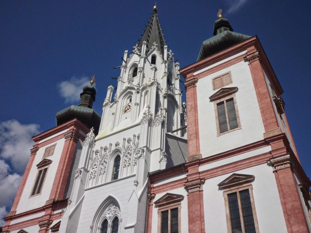 La façade principale présente une façade baroque avec une tour de style gothique en son centre.