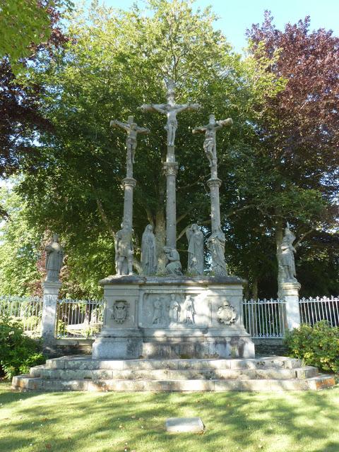 Trois colonnes portant le Christ, entre deux larrons, et au pied desquelles se trouvent Saint Longin le Centurion, la Vierge, saint Jean, Marie-Madeleine, et Marie-Salomé.