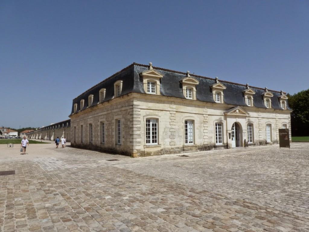 Un pavillon occupe chaque extrémité du long bâtiment, dont l'axe est marqué par une baie ornée d'un fronton triangulaire.