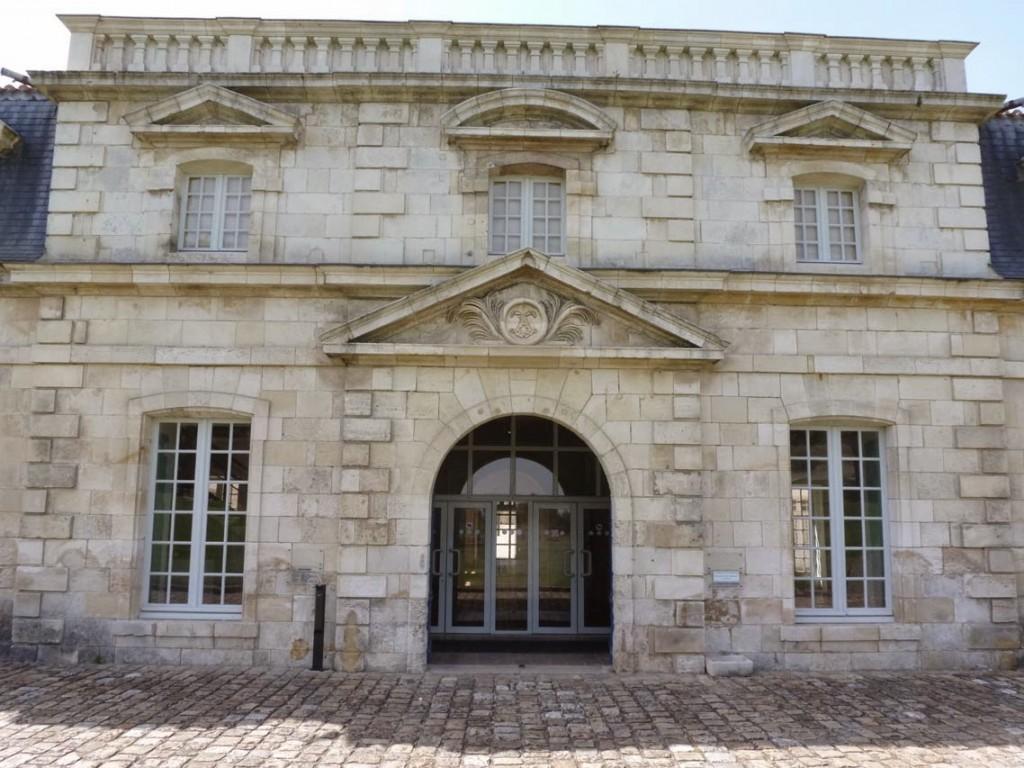 La façade du petit bâtiment est interrompu en son centre par la seule élévation à deux niveaux (Le fronton est décoré du monogramme de Louis XIV).