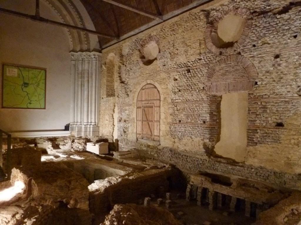 L'église primitive d'Entrammes a été construite dans les thermes antiques, dont les vestiges ont été découverts en 1987. (Sur la photo, depuis le mur de séparation avec le transept (à gauche): le frigidarium, le tepidarium et le sudatorium avec son hypocauste.)