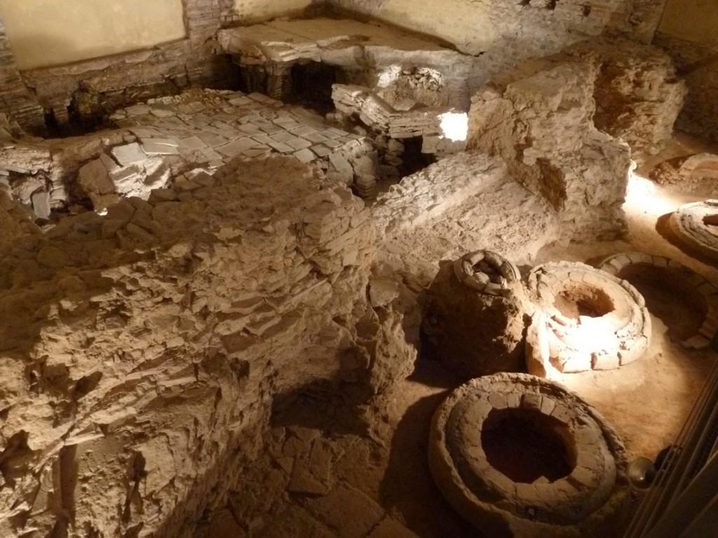Des vestiges de la construction de l'église sont également présents comme ces anciens moules à cloche. Derrière se trouve les restes du mur nord des thermes, et le caldarium dont la suspensura (sol au dessus de l'hypocauste) s'est effondré. Le côté Ouest de cette pièce chaude (en haut de la photo), était occupée par un bassin.