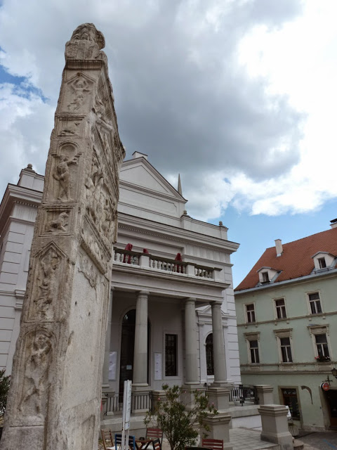 La stèle funéraire du IIe siècle orne la place principale de Ptuj, l'une des villes les plus anciennes de Slovénie. Derrière celle-ci, nous pouvons voir le théâtre municipal.