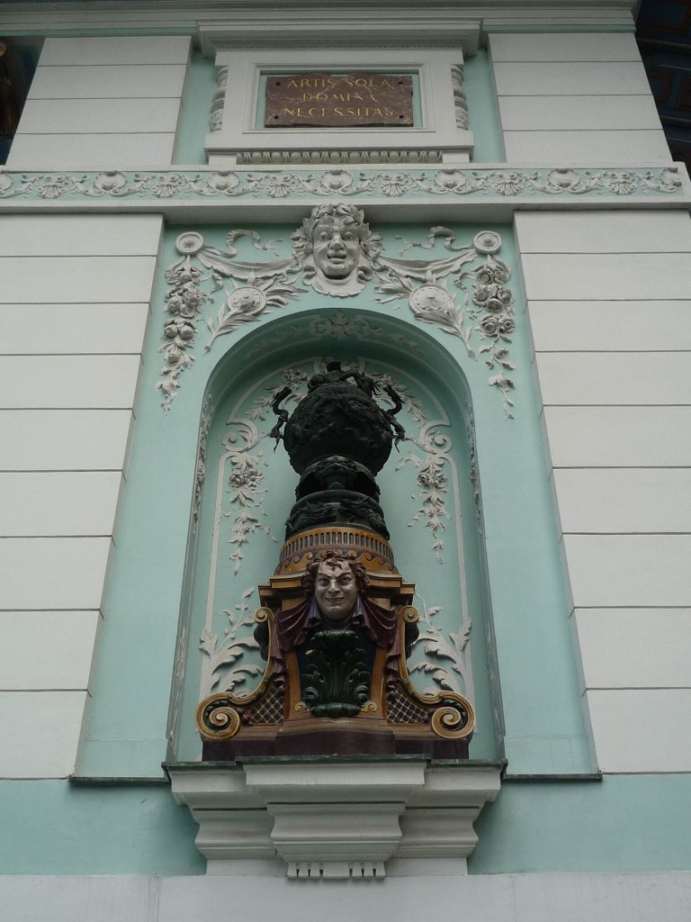 """Un des panneaux sur la façade principale, avec l'inscription """"Artis sola domina necessitas"""""""